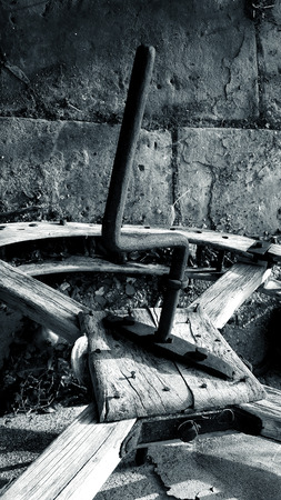 Old wooden wheel gear with rusty metal handle and brackets. Olive oil processing equipment. Garden wall, pomegranate.