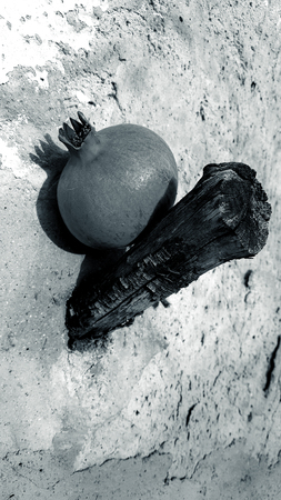Pomegranate sitting on an old wooden hook stuck in an old stone wall.