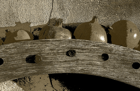Old wooden wheel gear with rusty metal handle and brackets. Olive oil processing equipment. Garden wall, pomegranates in evening sunshine. Monochrome, sepia tone, black and white. Imagens