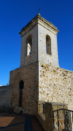 Old stone belltower with wooden door and metal cross. Blue clear sky.