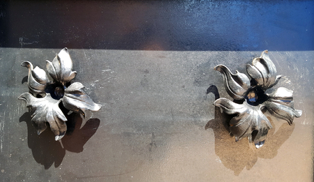Decorative metal flowers on a metal plate