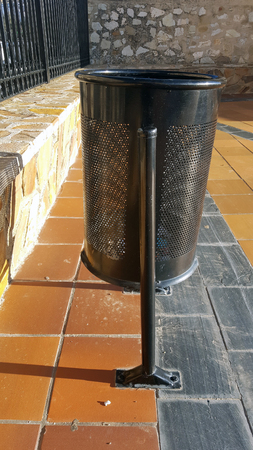 Tilting round black metal rubbish bin on tiles