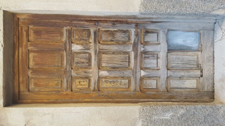 Wooden front door with decorative panels. Water damage at the bottom and brass lock and door knob. Marble step and pavement.