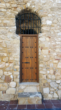 Heavy studded wooden door to a belltower set in a sandstone wall. Imagens