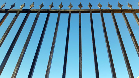 Black railings with pointed ends against a deep blue sky