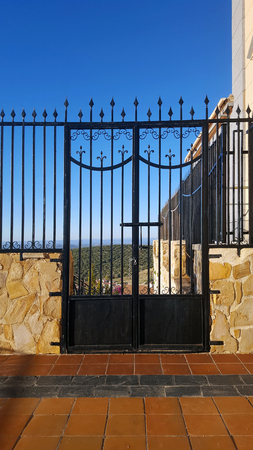 Martos, a white Spanish town from a high viewpoint. Black metal railings and gate. Imagens