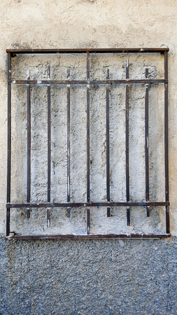 Bricked up window with metal bars in front