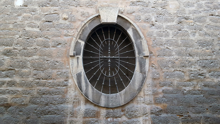 Old oval window with a metal grille set in a stone wall and staining on the wall