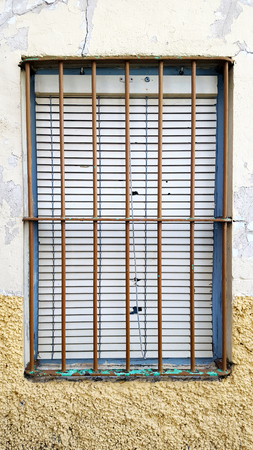 Old window with security bars, steel grill, decaying paint and yellow and white wall.