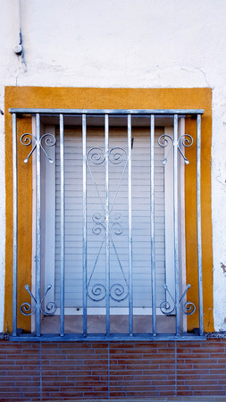 Old window with security bars, steel grill, yellow paint and brickwork.