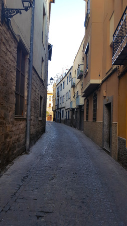 Narrow Spanish street with yellow walls and cobbles