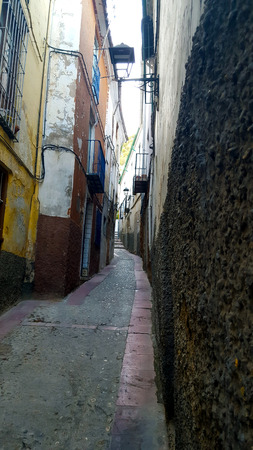 Narrow street in a Spanish town with decaying damaged walls.