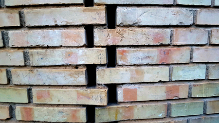 Brick wall with spaces set at an angle in a herringbone pattern.