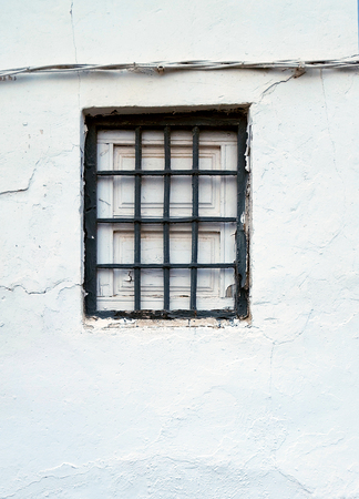 Old window with security bars, steel grill, grey and white paint and electricity cables.
