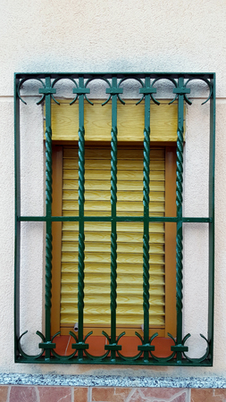 Old window with security bars, steel grill, green bars, yellow shutter, brickwork. Imagens