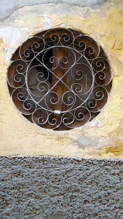 Round window in stone wall with metal grill and yellow painted wall.