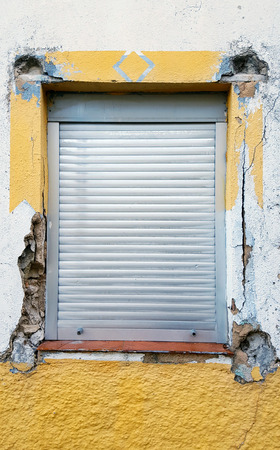 Old window with security bars, steel grill. Damaged wall and yellow paint.