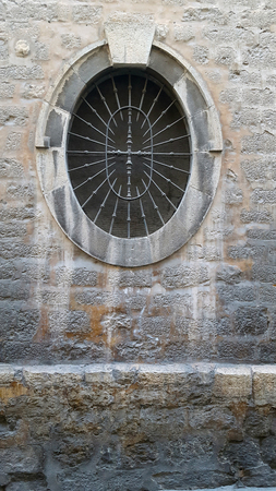 Old oval window with a metal grille set in a stone wall with staining on the wall