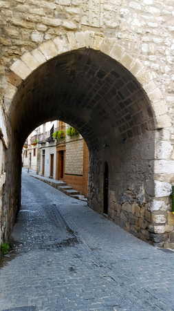 Stone arch on a narrow cobbled  street. Tunnel. Imagens