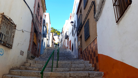 steps in a street with green railings and orange wall