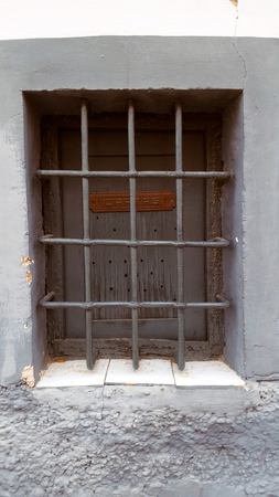 Old window with security bars, steel grill, grey wood and cartas sign.