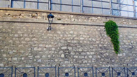 Stone wall by a road with railings and green plants, street light and metal panels