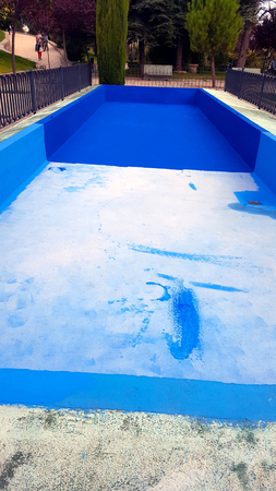 Blue ornamental pool in a park empty without water. Imagens