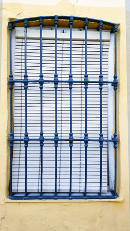 Old window with security bars, steel grill, yellow wall and blue bars
