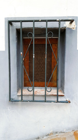 Old window with security bars, steel grill, mesh and brown paint