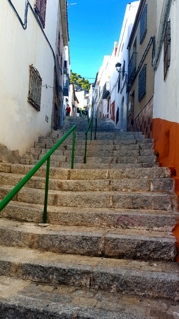 green railing on stone steps on a narrow street with blue sky Imagens
