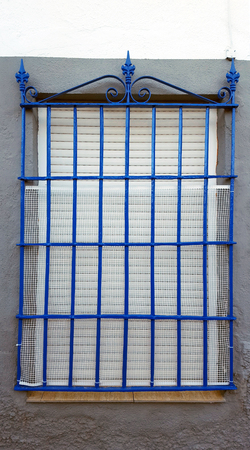 Old window with security bars, steel grill, blue bars, white plastic net and tile sill. Imagens