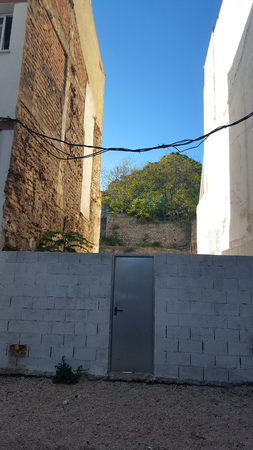Stainless steel metal door in a block wall with blue sky and trees. Imagens