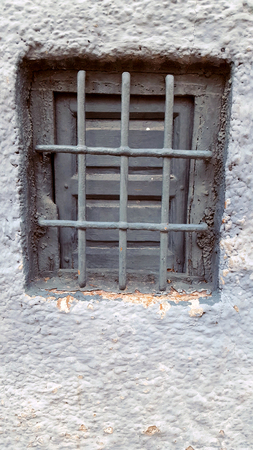 Old window with security bars, steel grill, grey and white paint Imagens