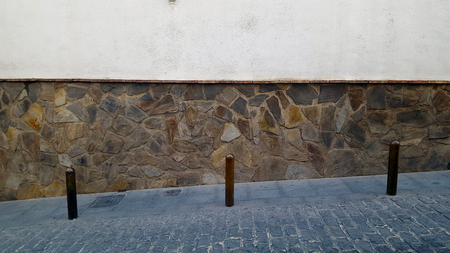 Metal bollards in a cobbled street with stone wall background Imagens