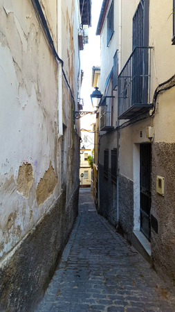 Narrow Spanish street with yellow walls and cobbles. Decaying walls.