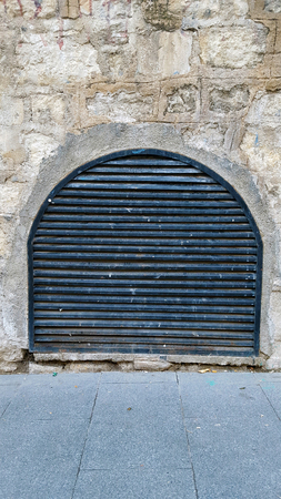 Metal grill ventilation cover in a stone wall.