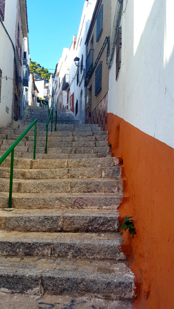 stairs in a Spanish street with blue sky and buildings Imagens