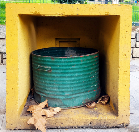 Round metal rubbish bin in a square yellow concrete box in a park Imagens