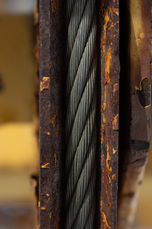 Fragment of old rusty construction equipment with a strong metal steel cable