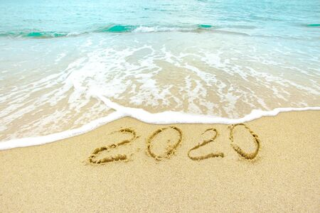 New Year 2020 on the sandy shore against the backdrop of sea waves.