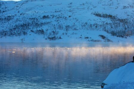 Winter landscape in the Arctic. The first rays of the rising sun illuminated the water surface of a cold lake. Majestic northern nature
