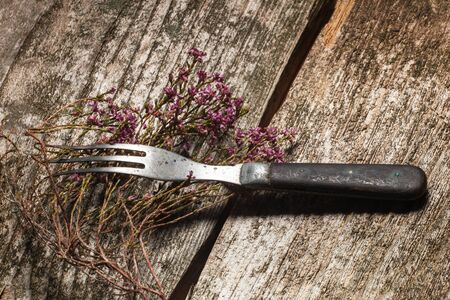 Antiquarian fork and dried flowers on an old wooden table