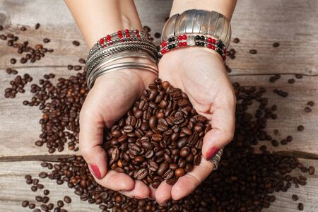 Women's hands in oriental jewelry hold a handful of coffee beans. Selective focus
