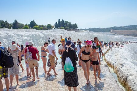 Pamukkale, Turkey- September 7, 2019: Numerous tourists walk on a sunny day on unique travertines.