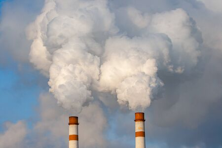 Clouds of smoke ascend from the pipes of an industrial enterprise against a blue sky