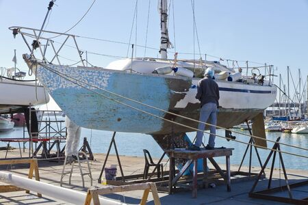 Yacht maintenance at the harbor. Preparation for painting.