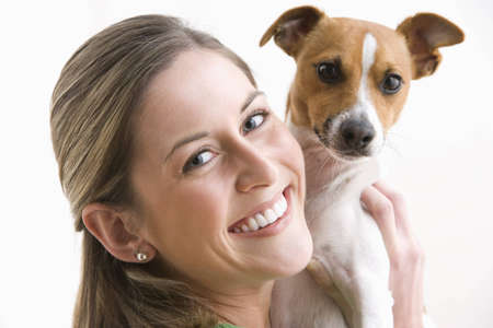 An attractive young woman is looking over her shoulder and smiling while holding a dog. Horizontal shot. Stock Photo
