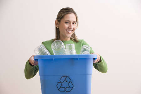 An attractive young woman his smiling and holding a blue recycle bin with plastic bottles in it. Horizontal shot.