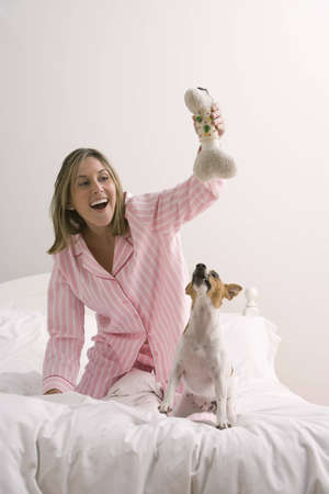 An attractive young woman wearing pink pajamas is holding a dog toy and playing with her terrier on a bed. Vertical shot.