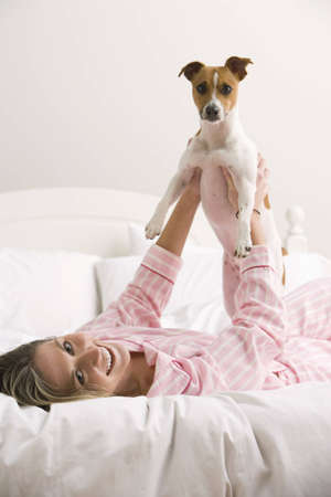 An attractive young woman wearing pink pajamas is holding a dog while laying on a bed. Vertical shot.